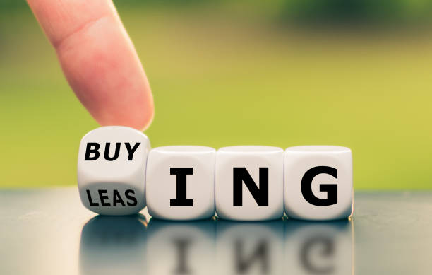 """Hand turns a dice and changes the word """"leasing"""" to """"buying"""", or vice versa. stock photo"""