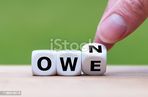 Hand turns a dice and changes the word