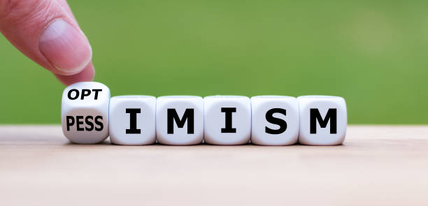 """Hand turns a dice and changes the word """"pessimism"""" to """"optimism"""". stock photo"""