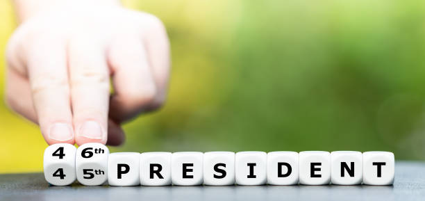 """Hand turns dice and changes the expression """"45th president"""" to """"46th president"""". stock photo"""