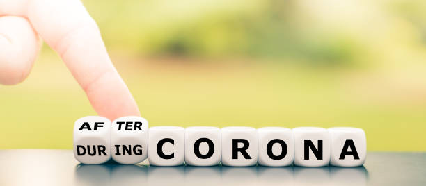 """Hand turns dice and changes the expression """"during Corona"""" to """"after Corona"""". stock photo"""