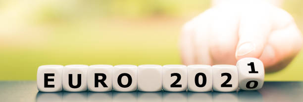 """Hand turns dice and changes the expression """"Euro 2020"""" to """"Euro 2021"""". stock photo"""