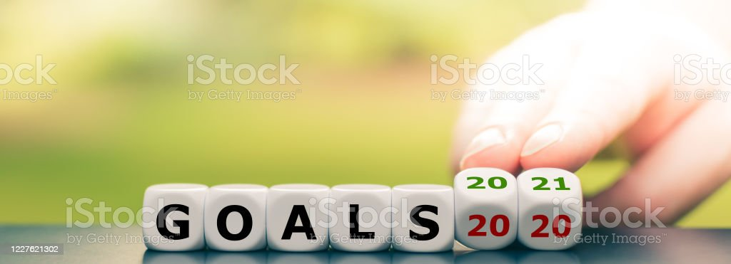 """Hand turns dice and changes the expression """"goals 2020"""" to """"goals 2021"""" Hand turns dice and changes the expression """"goals 2020"""" to """"goals 2021"""" 2020 Stock Photo"""