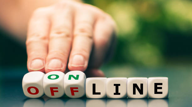 """Hand turns dice and changes the expression """"offline"""" to """"online"""". stock photo"""