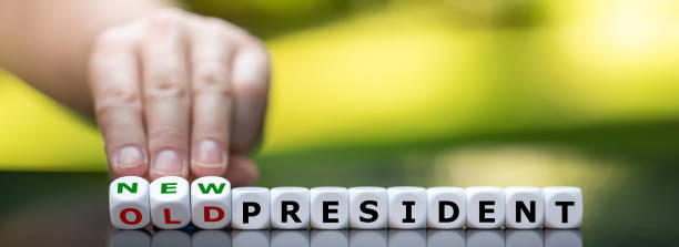 """Hand turns dice and changes the expression """"old president"""" to """"new president"""". stock photo"""
