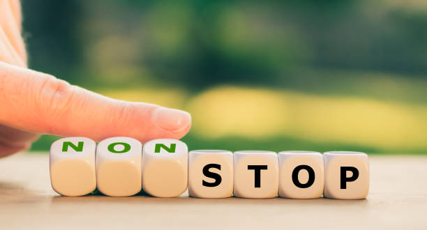 """Hand turns dice and changes the expression """"stop"""" to """"nonstop"""". stock photo"""