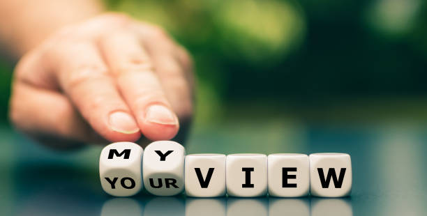 """Hand turns dice and changes the expression """"your view"""" to """"my view"""". stock photo"""