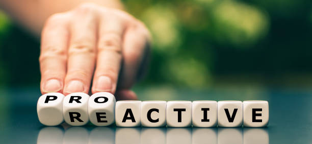 Hand turns dice and changes the word reactive to proactive. stock photo