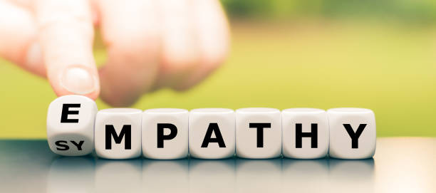 """Hand turns dice and changes the word """"sympathy"""" to """"empathy"""". stock photo"""