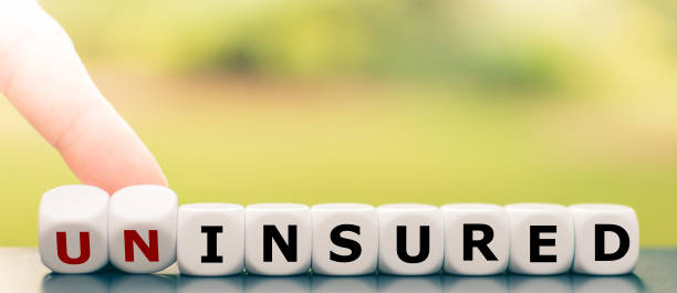 """Hand turns dice and changes the word """"uninsured"""" to """"insured"""". stock photo"""