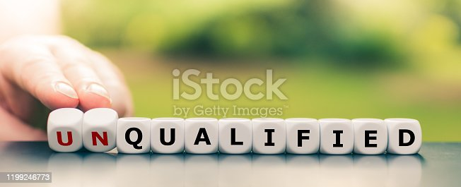 Hand turns dice and changes the word unqualified to qualified.