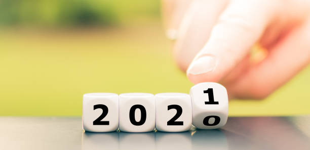 """Hand turns dice and changes the year """"2020"""" to """"2021"""". stock photo"""