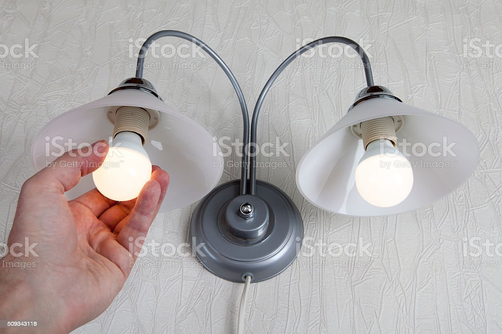 Hand twists led lightbulb in a lamp on white wall stock photo