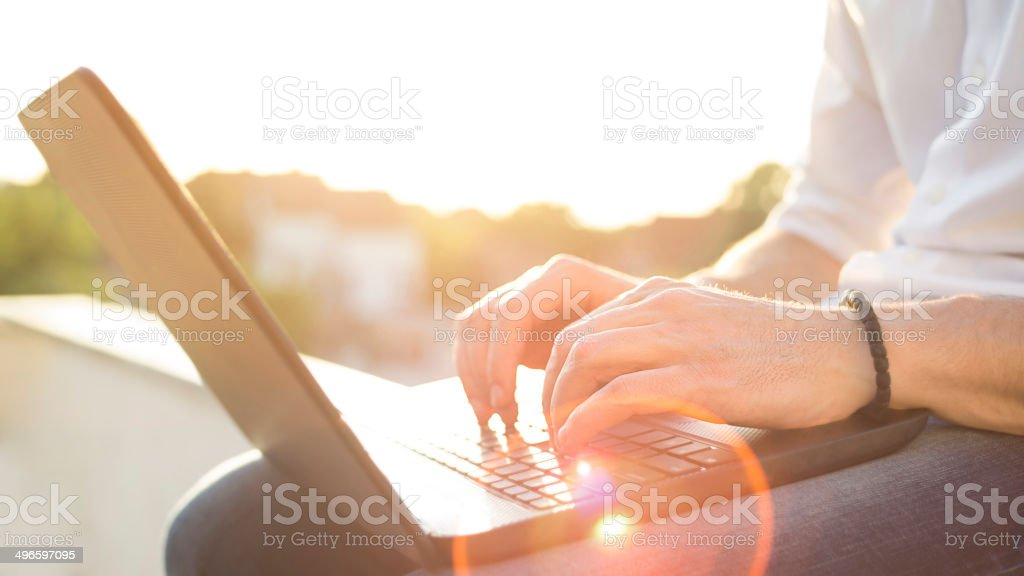 Hand typing on a laptop in sunset stock photo