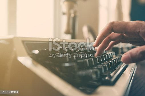istock Hand typing on an vintage typewriter. 517688314