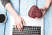 Hand typing on laptop and holding heart shape donut