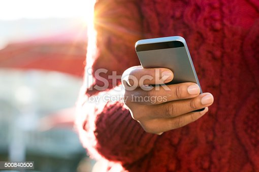 istock Hand typing on phone 500840500