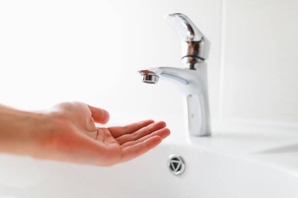mano debajo del grifo sin agua - presión fotografías e imágenes de stock