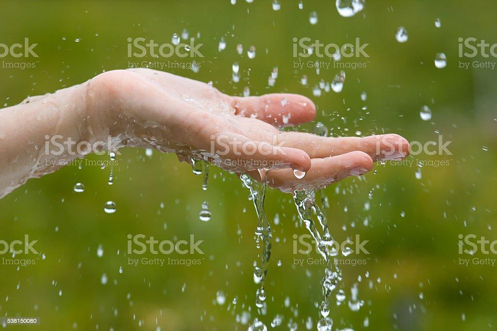 hand under rain stock photo