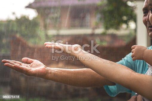 Kid enjoying rain drops with grand father