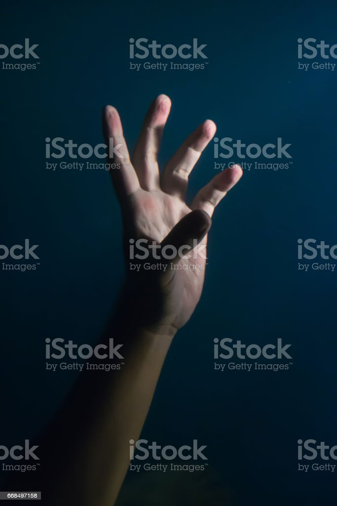 Hand under the water at night stock photo