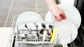 A hand reaches into a dishwasher. unloading clean dishes.