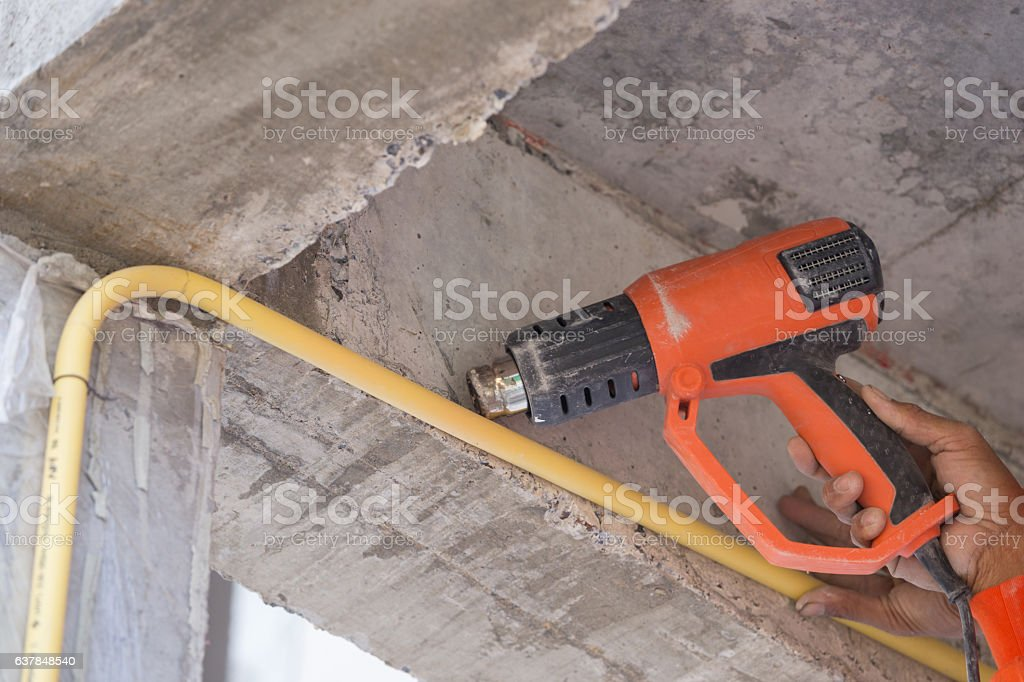 Hand use a heat gun to bending electric PVC pipe stock photo