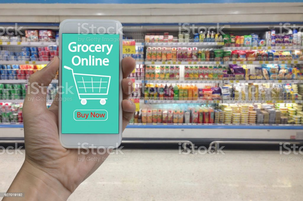 Hand use smartphone with grocery online on screen over blurred supermarket and retail store in shopping mall interior background stock photo