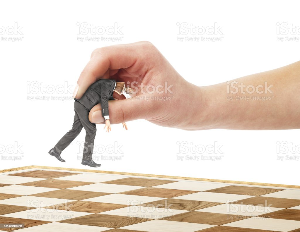 A hand uses as a pawn a businessman on a chessboard royalty-free stock photo