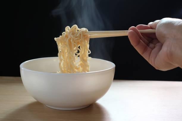 hand verwendet stäbchen abholen heißen instant-nudeln und rauch steigt auf schwarzem hintergrund - schnelle suppen stock-fotos und bilder