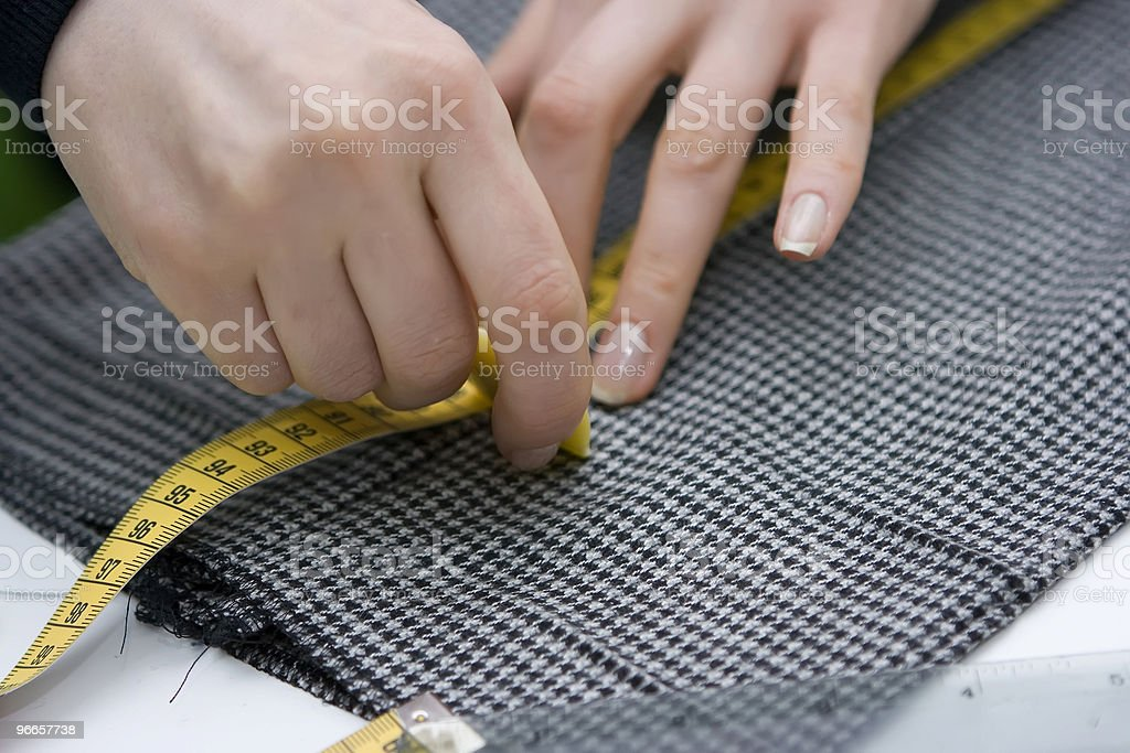 Hand using a measuring tape to measure a cloth stock photo