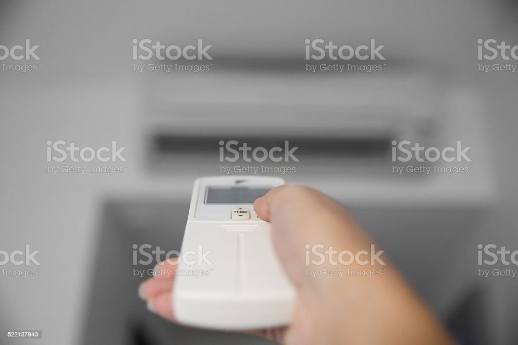 Hand using a remote to activating air conditioning machine stock photo