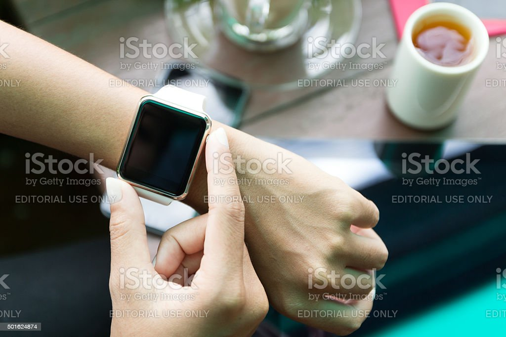 Hand using Apple Watch in coffee shop stock photo