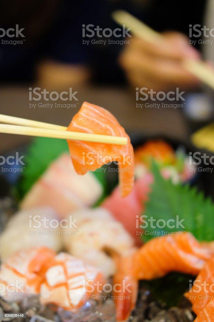 Hand using chopsticks pick fresh salmon stock photo