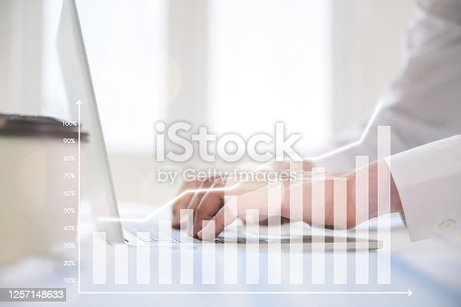 1051659174 istock photo Hand using computer laptop analysing sales data and economic growth graph chart. Business strategy development to success and growing concept. Digital marketing 1257148633