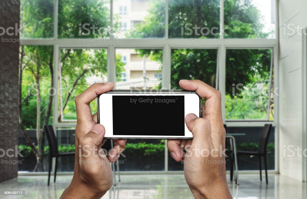 Hand using mobile phone, blank copy space on screen, interior living space background stock photo