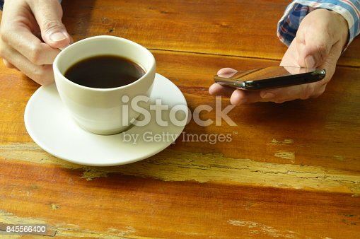 istock hand using mobile phone while drinking black coffee 845566400