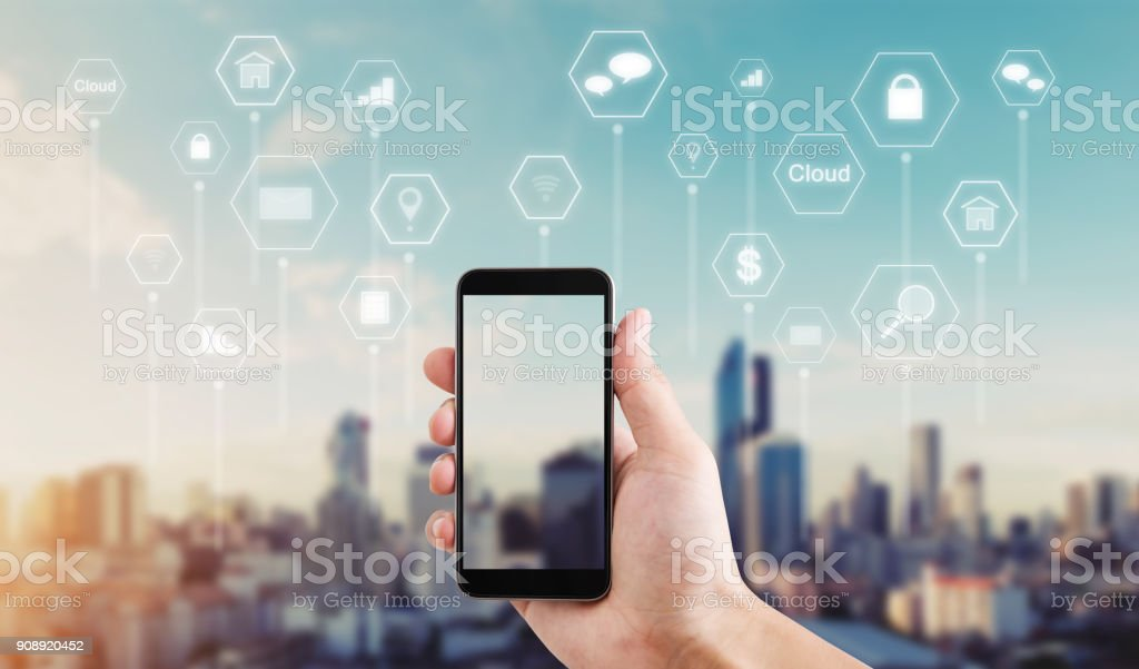 Hand using mobile smart phone with application icons such as online message, internet payment, banking, online shopping and etc. city sunrise background stock photo