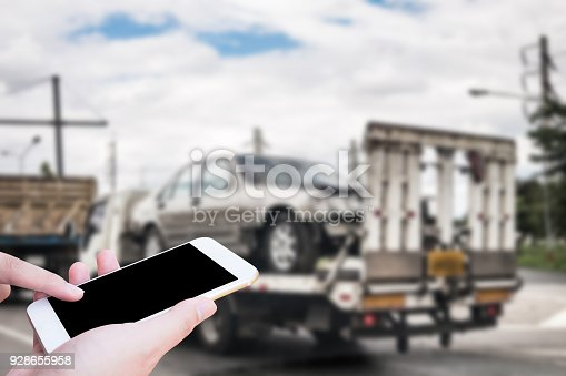 istock Hand using mobile smartphone for emergency roadside service with Broken car on tow truck after traffic accident background 928655958