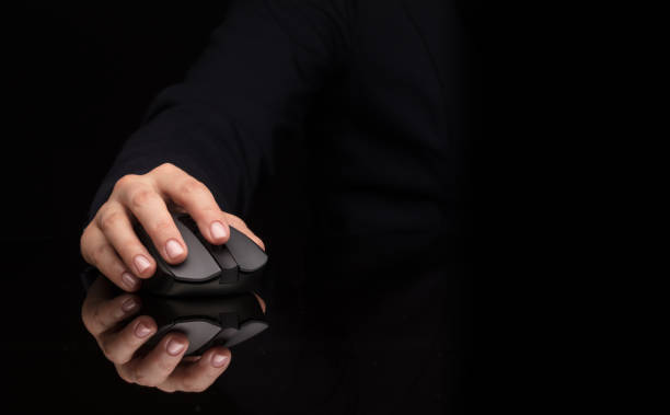 Hand using mouse on dark background stock photo