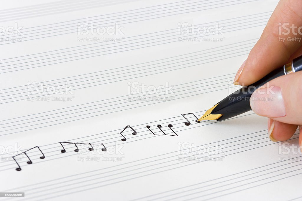 Hand using pencil to write musical notes on sheet music stock photo