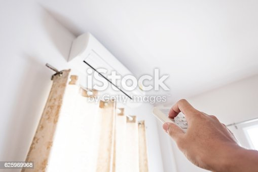 istock Hand using remote control air conditioning, representing energy saving concepts 625969968