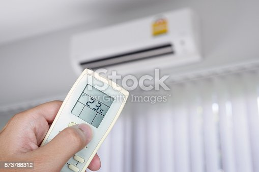 istock Hand using remote control with air conditioner in the room 873788312