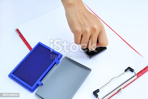 683496662 istock photo Hand using rubber stamper with blue Ink pad(box) on white paper. 683496940