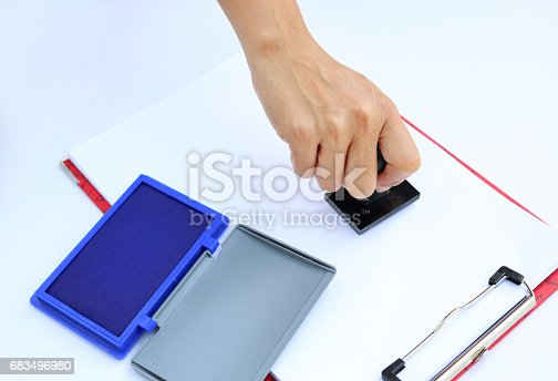 683496662 istock photo Hand using rubber stamper with blue Ink pad(box) on white paper. 683496980
