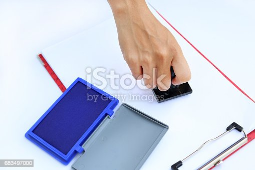 istock Hand using rubber stamper with blue Ink pad(box) on white paper. 683497000