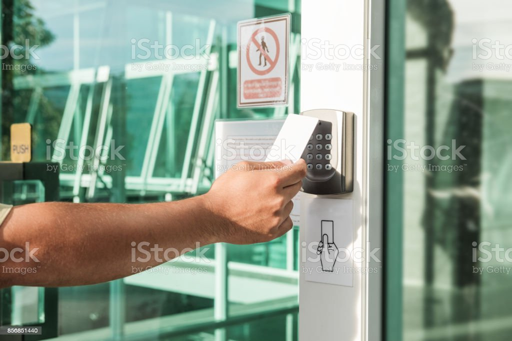 Hand using security key card scanning to open the door to entering private building. Home and building security system stock photo
