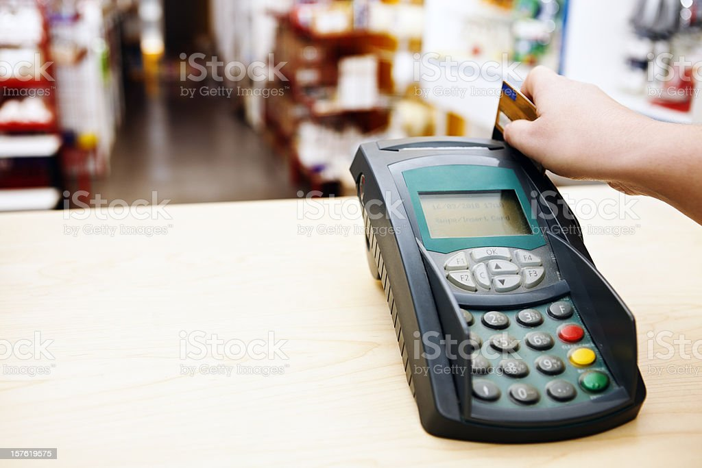 Hand using smart card reader with store in background royalty-free stock photo