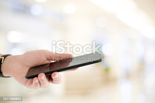 istock Hand using smart phone over blur bokeh light background, business and technology, internet of things concept 1011085652