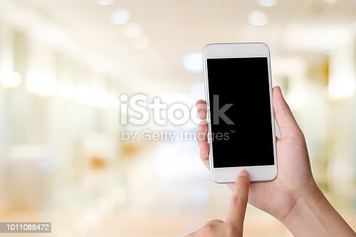 istock Hand using smart phone over blur bokeh light background, business and technology, internet of things concept 1011088472